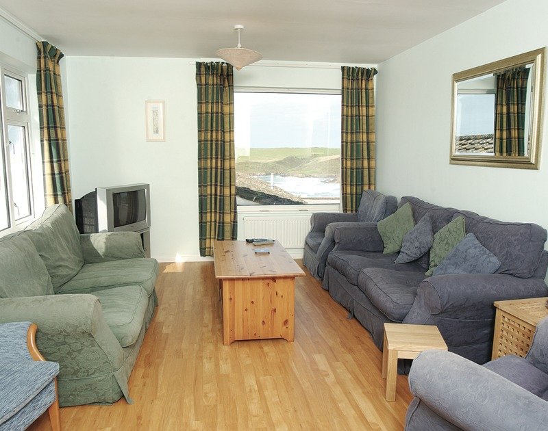 The comfortable sitting room with superb sea views at Trevic, a self catering holiday rental in Polzeath, Cornwall.