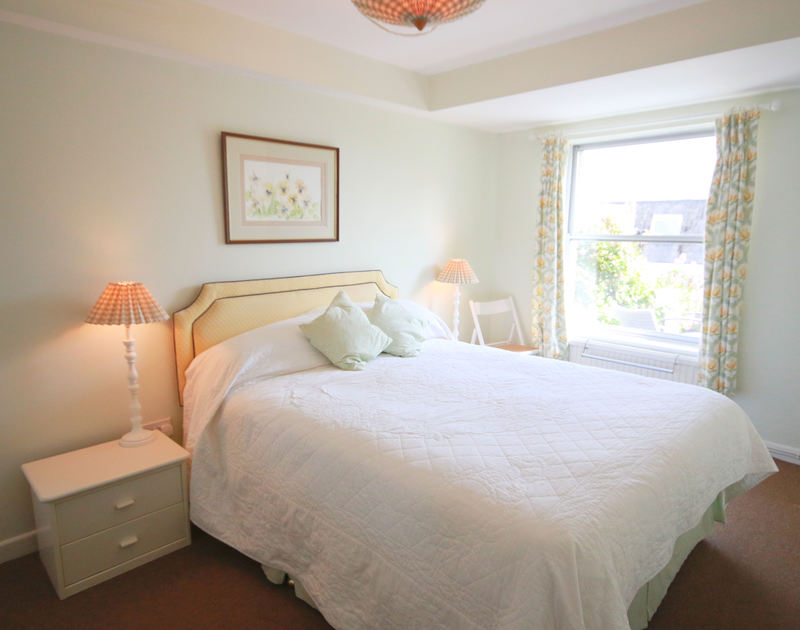 The master tastefully furnished king size bedroom in Slipway 12, a comfortable self catering holiday cottage to rent in Rock, Cornwall.