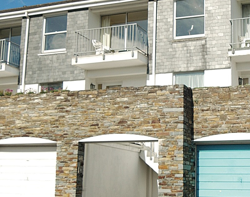 The exterior of Slipway 16, a terraced holiday cottage in Rock, Cornwall, with its first floor balcony.
