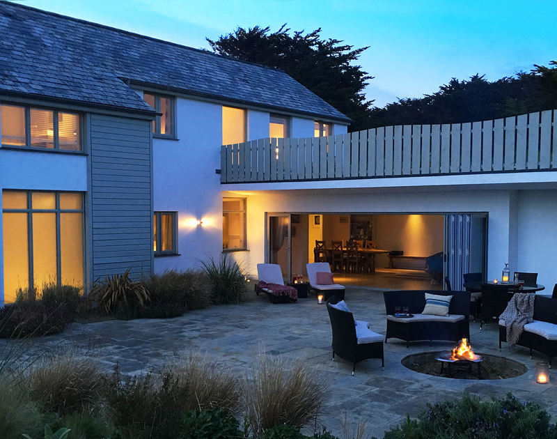 Atmospheric lighting at Downalong, a self-catering luxury holiday house at Daymer Bay, Cornwall, with glowing fire pit.
