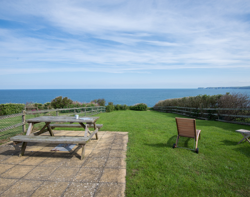 Beautiful views of the sea from the large garden and terrace stretching towards the cliffs at Coastguard Cottage 3, a clifftop holiday house to rent in Port Isaac, Cornwall.