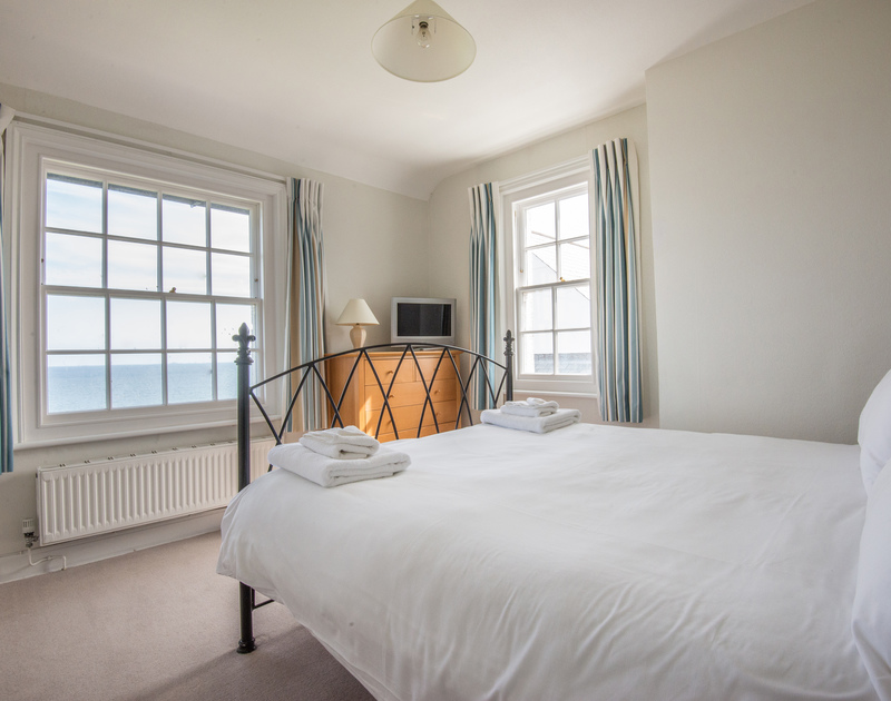Master bedroom with King size bed facing towards windows with fantastic sea views in Coastguard Cottage 3, a self catering holiday house to rent on the clifftop above Port Isaac in North Cornwall.