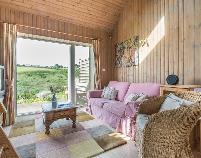 South facing french doors open out on to a sun deck overlooking the valley from the living room at self catering holiday rental Cartway Cabin at Port Gaverne, Cornwall.