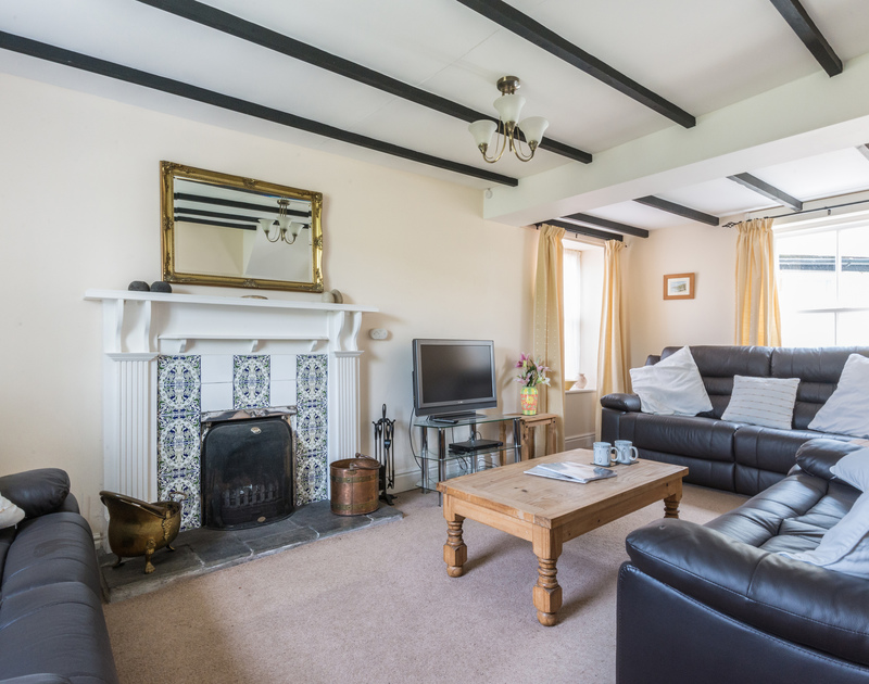 Comfortable and cosy sitting room with open fire place at Morwenna, a holiday house in Port Isaac, Cornwall