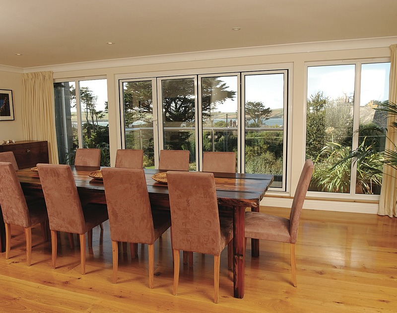 The smartly furnished dining room of Bodare 8, holiday apartment at Daymer Bay, with doors to the balcony.