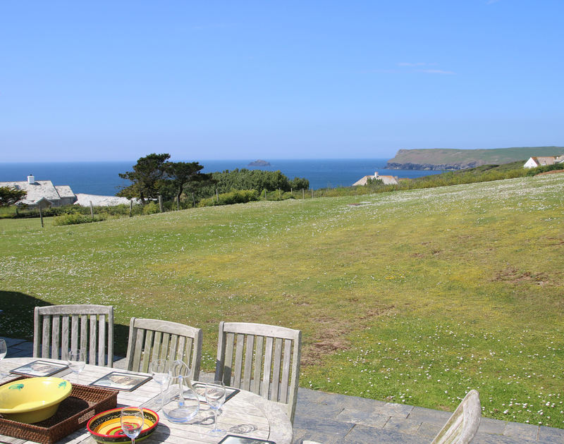 The sunny outside table and chairs with sea views at Tristan, holiday rental near Daymer Bay, Cornwall, with its large garden.