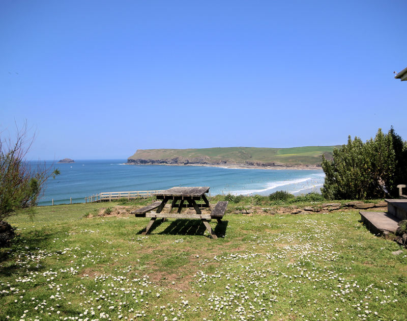 Sea and coastal views from the garden of Kittiwake, a holiday cottage in Rock, Cornwall, with its picnic table.