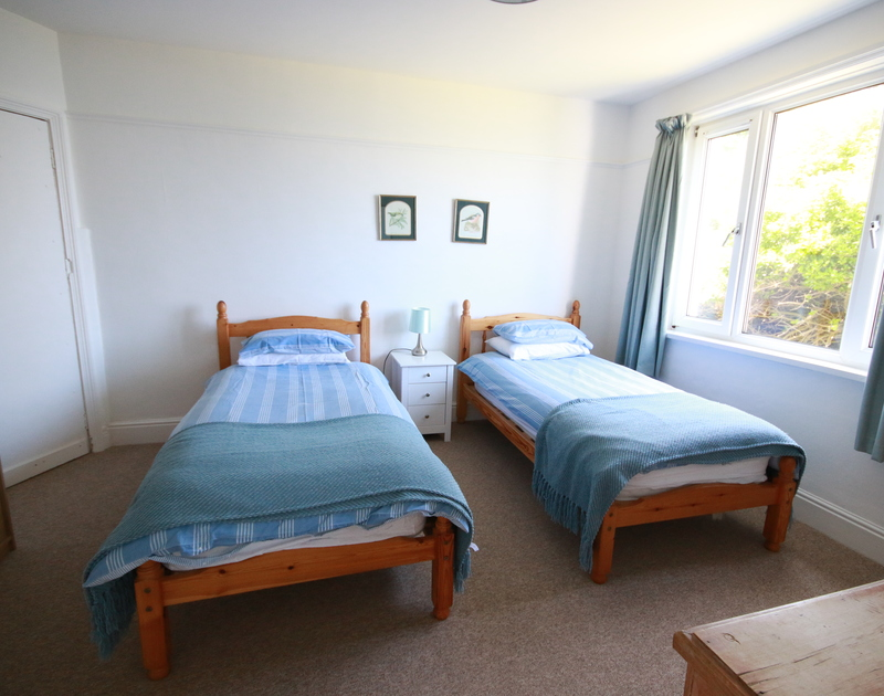 One of two twin bedrooms at Kittiwake, a holiday cottage by the beach in Polzeath, Cornwall