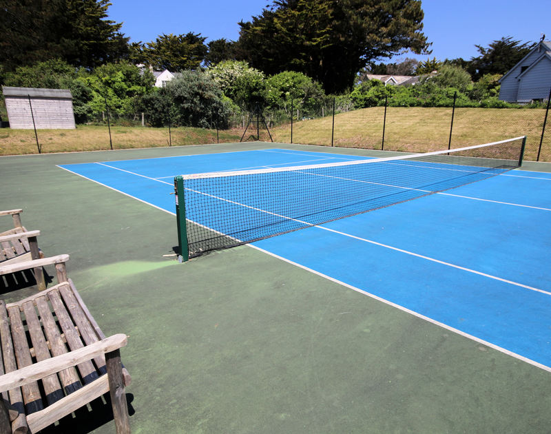 The tennis court at Downalong, a fantastic, luxury holiday house at Daymer Bay, Cornwall, with spectator benches.
