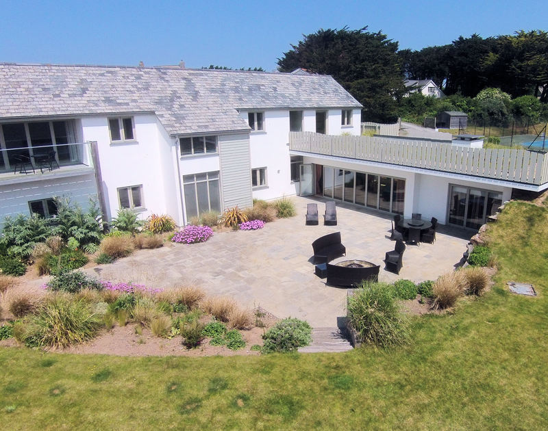 The large terrace of Downalong, a stunning, self-catering holiday house at Daymer Bay, Cornwall, with its fire pit and surrounding garden borders.