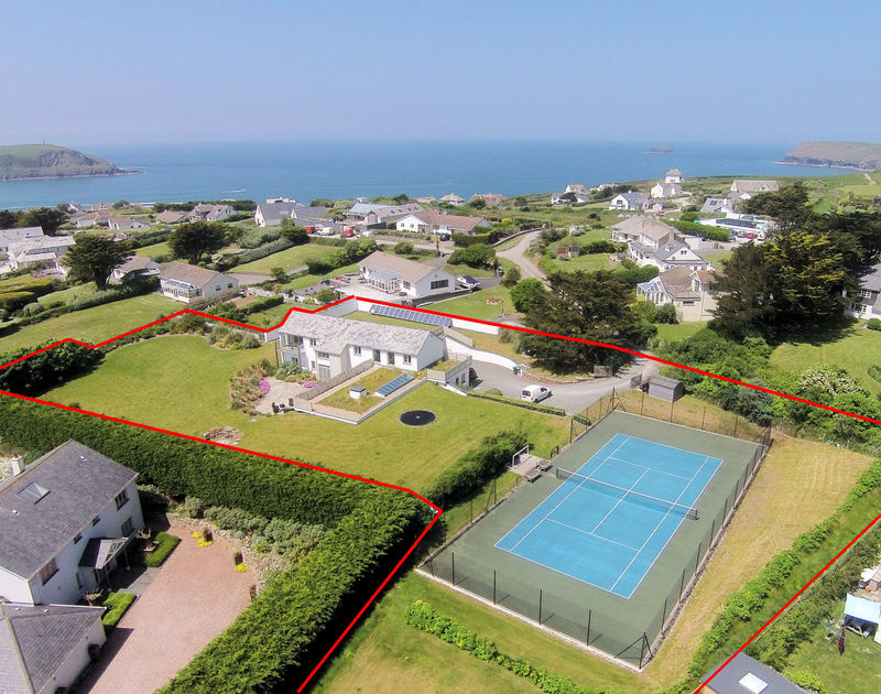 An aerial view of Downalong, a luxury holiday house at Daymer Bay, Cornwall,  with its tennis court and large garden.