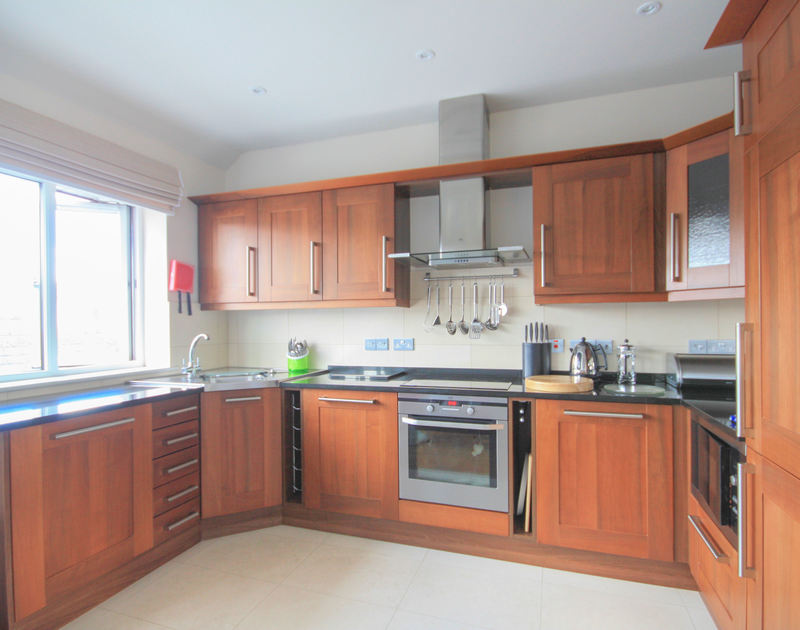 Smart, glossy kitchen at Number 9, Port Isaac, with ample work surfaces