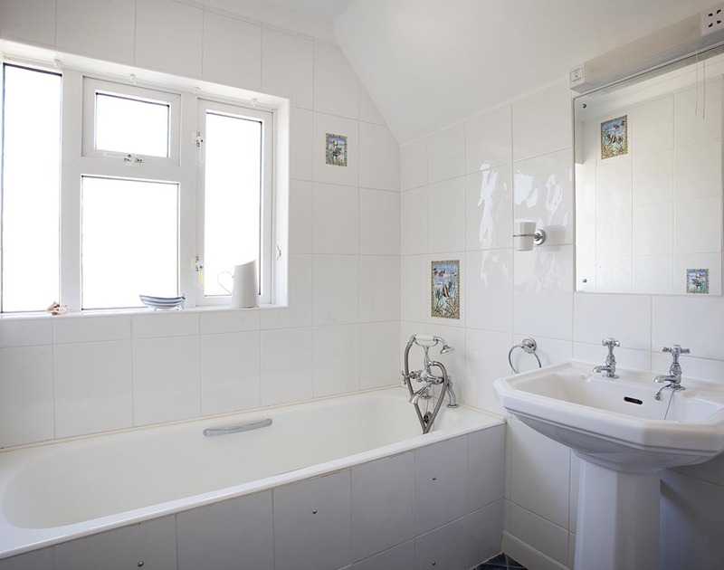 The bright, white bathroom for the master bedroom at Bay View Cottage in Daymer Bay.