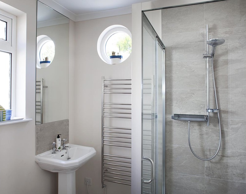 The ground floor shower room at Bay View Cottage in Daymer Bay has a porthole window.