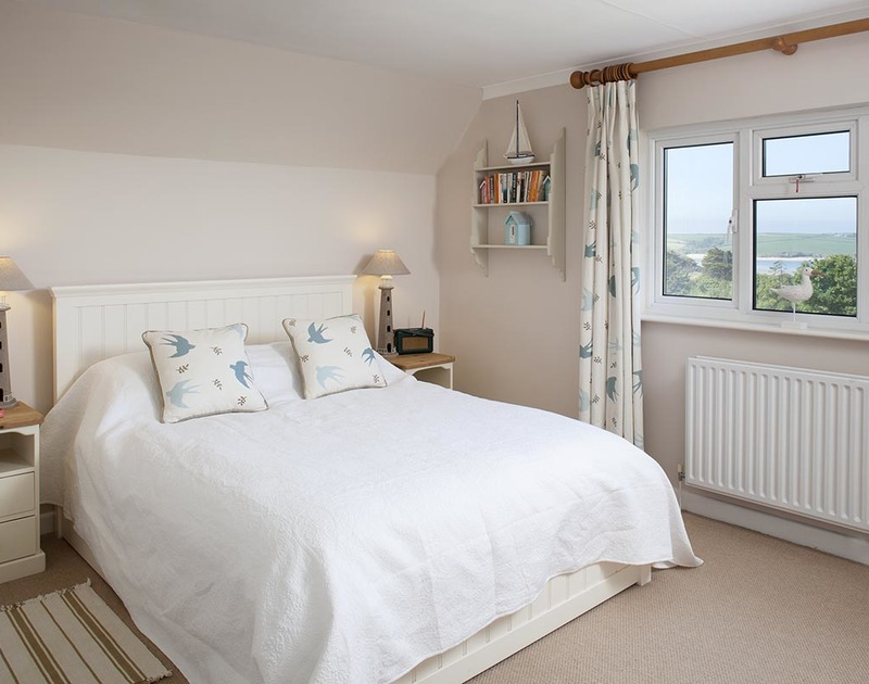 The sea views and pretty Vanessa Arbuthnott fabric adorning the cushions and curtains make the master bedroom in Bay View Cottage a relaxing and restful place to be,