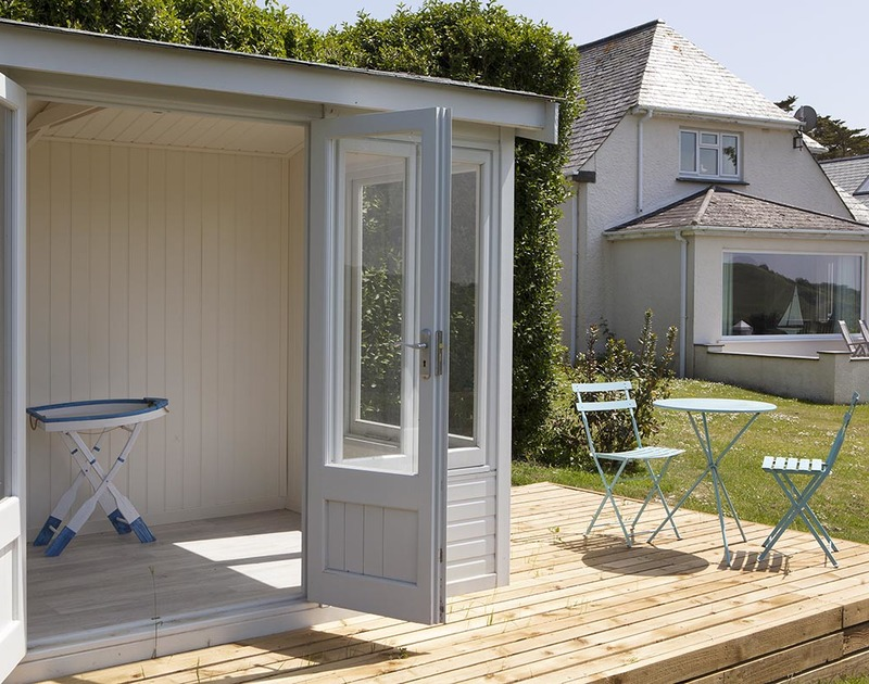 The pretty summer house at Bay View Cottage has a decked area and garden furniture, perfect for morning tea or evening drinks after a busy day on the beach at Daymer Bay.