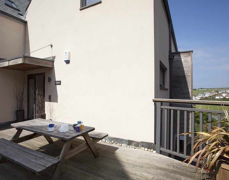 The decked terrace at Kellan, a luxury holiday house in Polzeath, Cornwall, with picnic table.