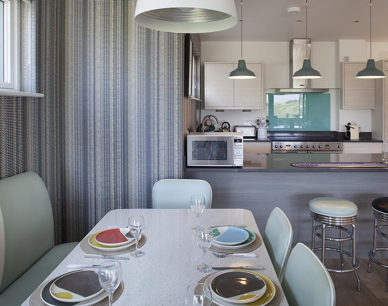 The stylish kitchen/diner at Kellan, a superb self-catering holiday rental in Polzeath, Cornwall, with breakfast bar.