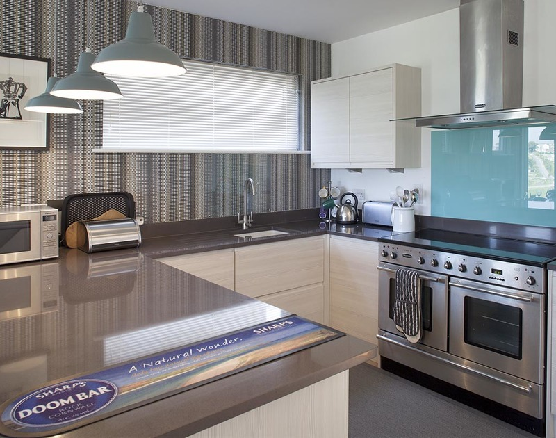 The sleek kitchen at Kellan, a luxury holiday house in Polzeath, Cornwall, with ample work surface and double oven.