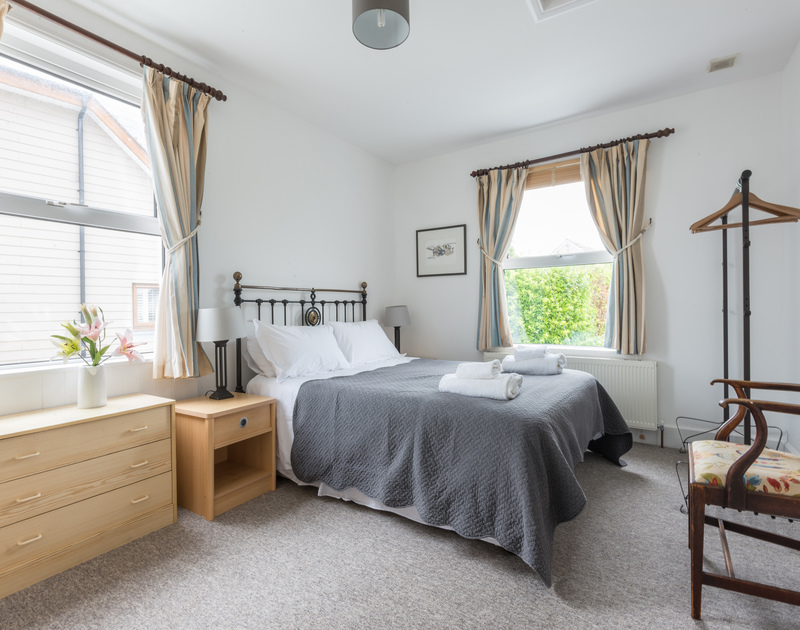The spacious master bedroom with king size bed and en-suite shower room at Signal Post, luxury self catering holiday accommodation in Port Isaac, North Cornwall.