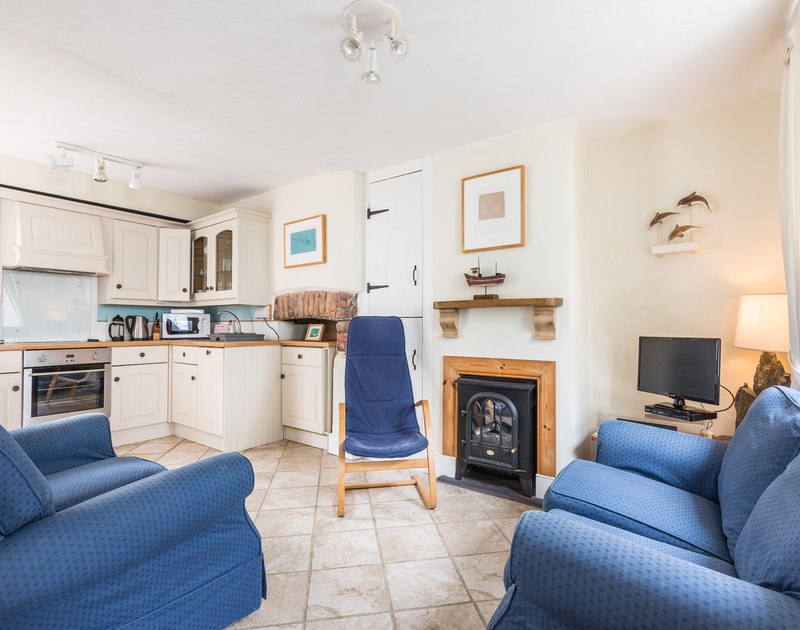 Cosy open plan living room/kitchen of Brakestone Cottage, Port Isaac, with stable door out on to front patio.