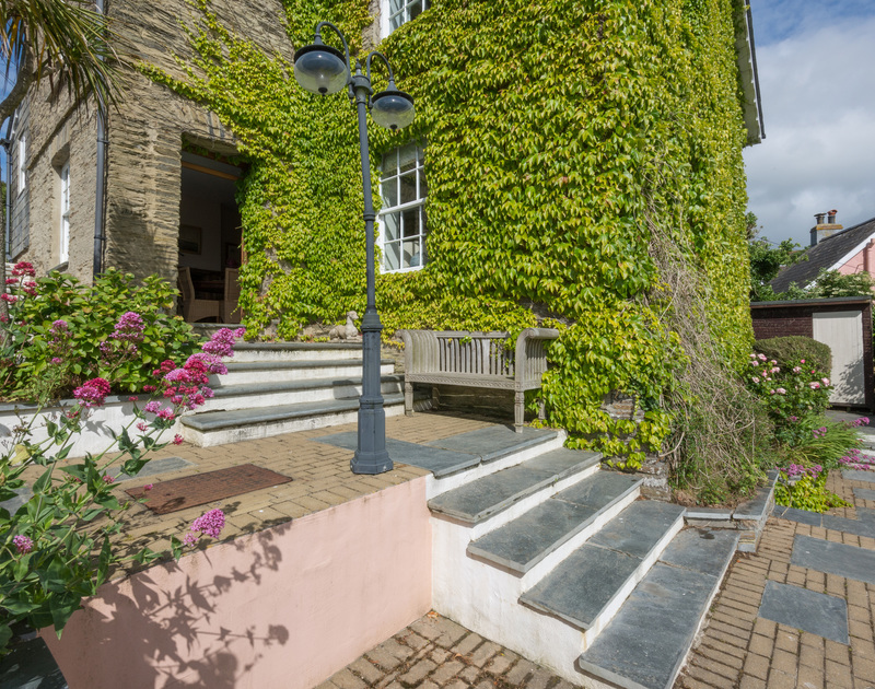The ivy-clad exterior of Valencia House, a self-catering holiday house in Port Isaac, Cornwall, with steps up from the terrace.
