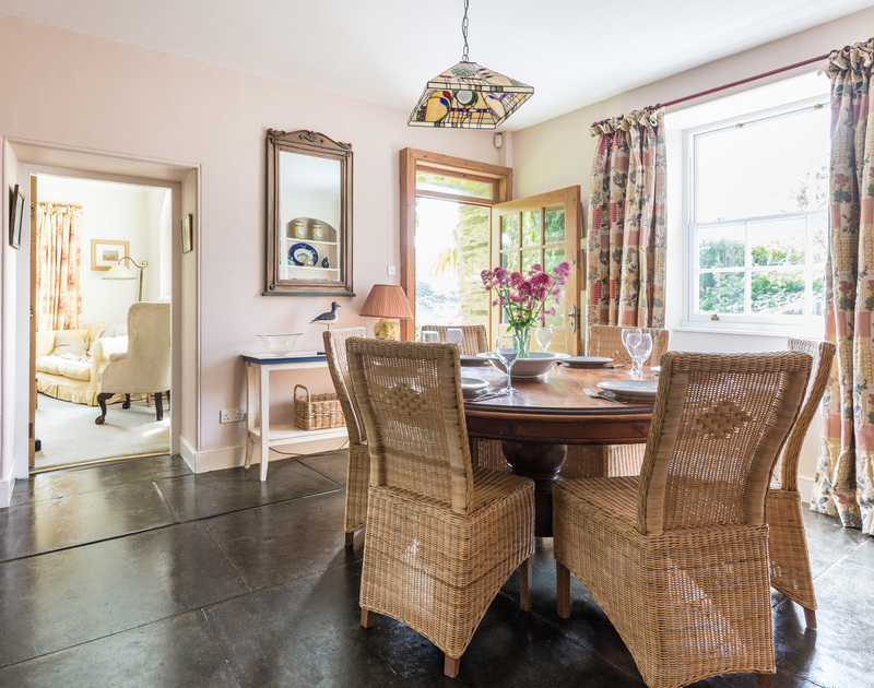 The elegantly furnished dining room at Valencia House, a holiday rental in Port Isaac, with its slate floors and door to garden.