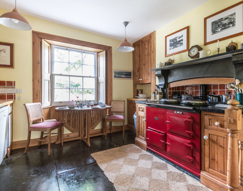 Traditional features in the kitchen of Valencia House, Port Isaac, include an Aga, slate floors and sash window.