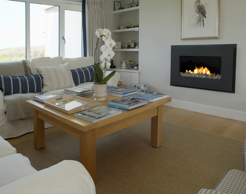 The comfortable, contemporary sitting room with modern fireplace at Greenaway Heights, a luxury holiday house near Daymer Bay, Cornwall