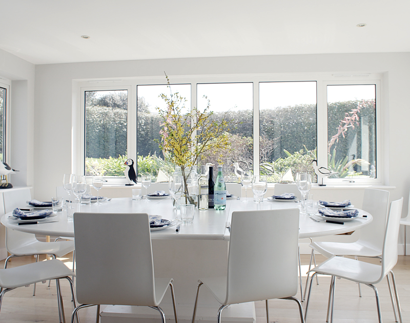 The sunny, formal dining room with doors to the patio at Greenaway Heights, a luxurious coastal holiday house to rent near Daymer Bay, Cornwall