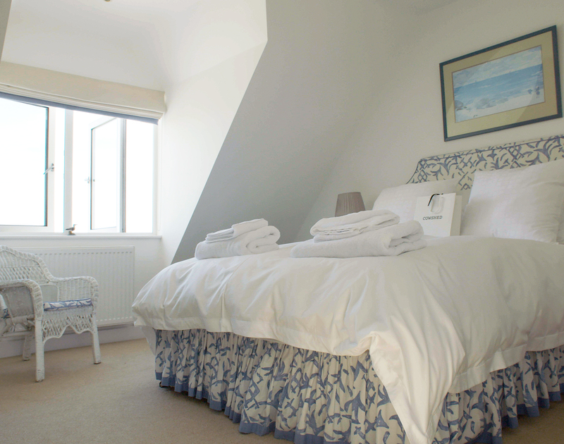 This airy king size bedroom at Greenaway Heights has stunning sea views of Stepper Point and an adjacent bathroom