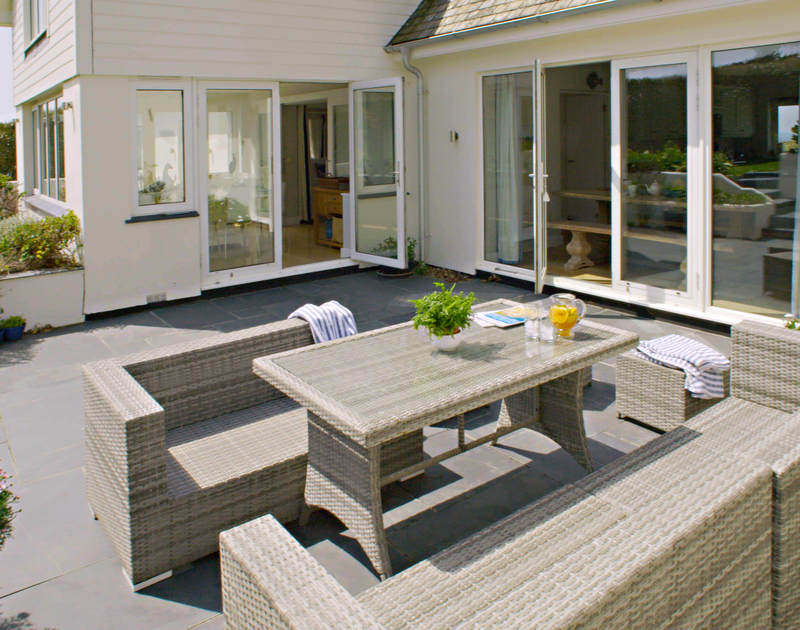 Unwind outside on the sunny patio with easy access to the kitchen and dining room at Greenaway Heights, Daymer Bay.