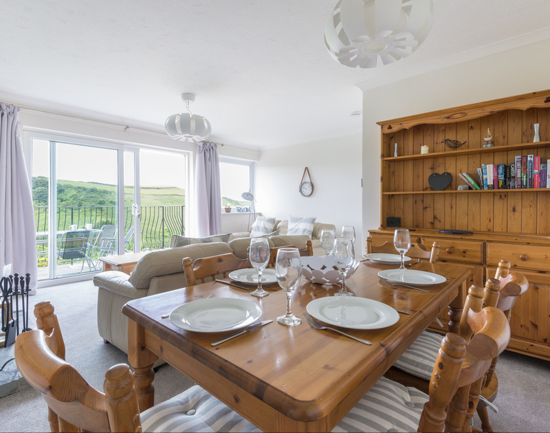 Open plan sitting room and dining area with valley and sea views and access to the garden.