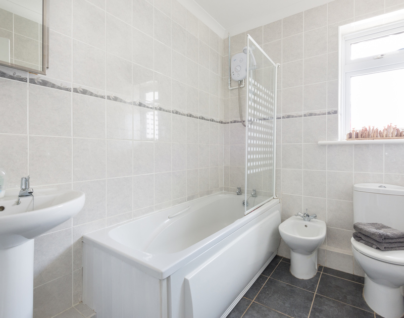 Bright and contemporary family bathroom with a bath and shower attachment.