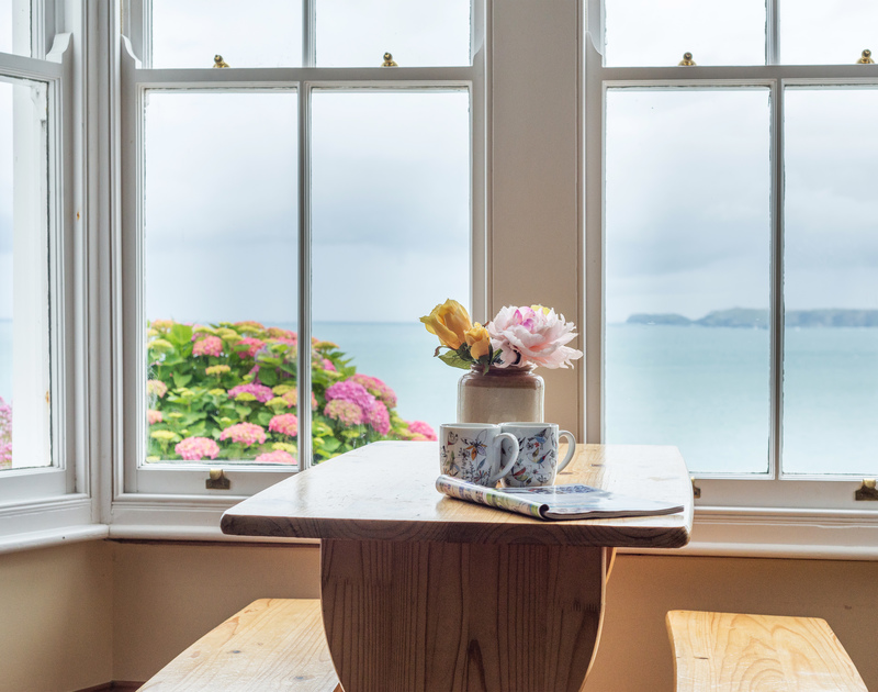Stunning sea views through the pretty sash windows from the  sitting room at Seaward, self catering holiday accommodation overlooking Port Gaverne in Port Isaac in Cornwall.