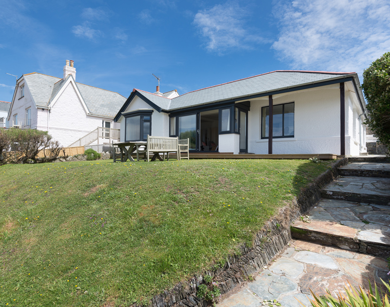 The exterior of Low Cliff Cottage, a self-catering holiday house in Polzeath, Cornwall, with sloping lawned garden.