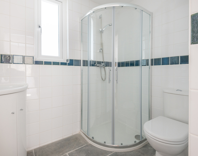 Fully-tiled ensuite shower room at Low Cliff Cottage, a holiday house in Polzeath, Cornwall