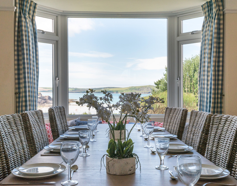 Seaviews through the picture window of the dining room of Low Cliff Cottage, a seaside holiday cottage in Polzeath, Cornwall