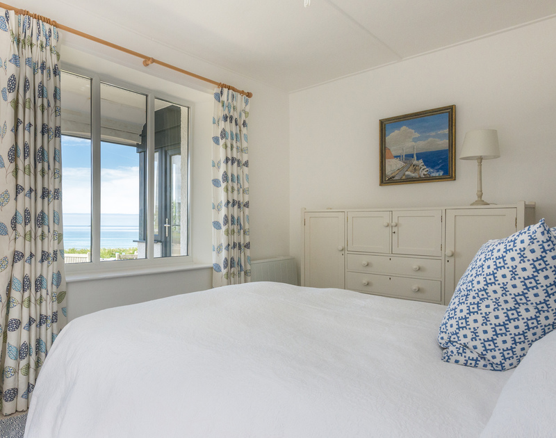 The comfy double bedroom of Low Cliff Cottage, a holiday cottage in Polzeath, Cornwall, with glorious seaviews.
