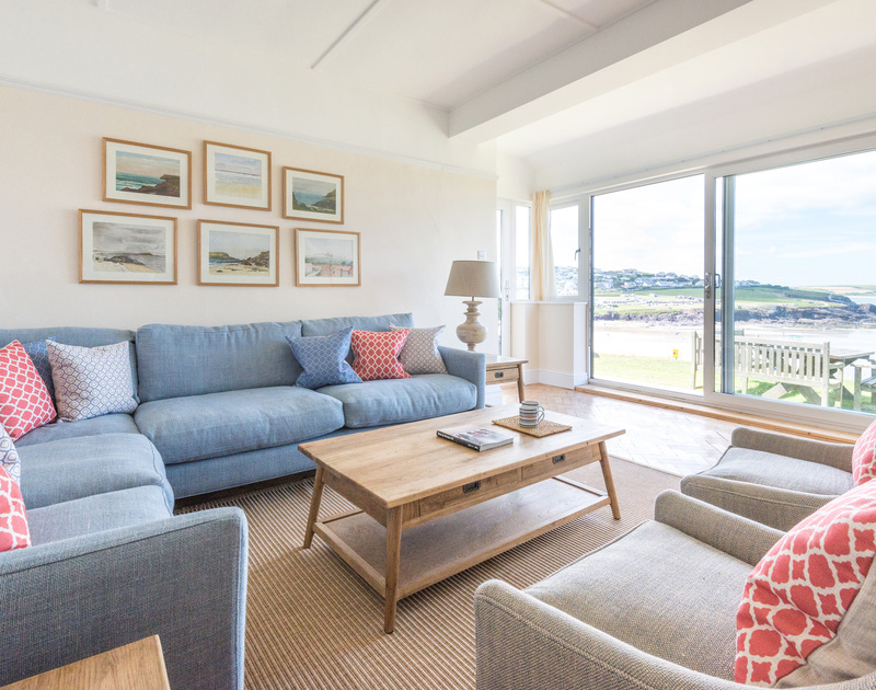 Seaviews from the stylish sitting room of Low Cliff Cottage, a holiday cottage in Polzeath, Cornwall, with large corner sofa and armchairs.