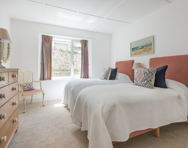 Restful and chic twin bedroom of Low Cliff Cottage, a holiday rental in Polzeath, Cornwall, wth chest of drawers.