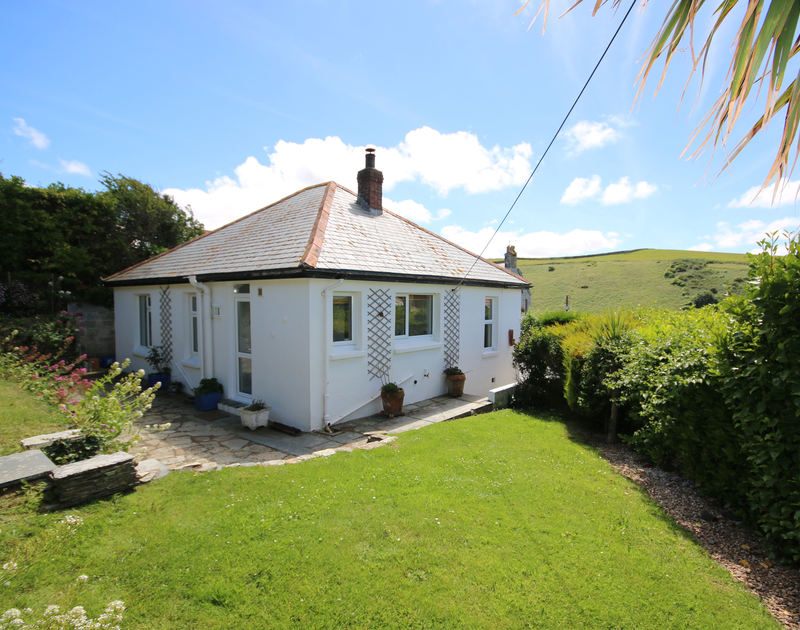 Rear patio and lawned side garden with the exterior of the self catering holiday house Tamarisk in Port Isaac, Cornwall.