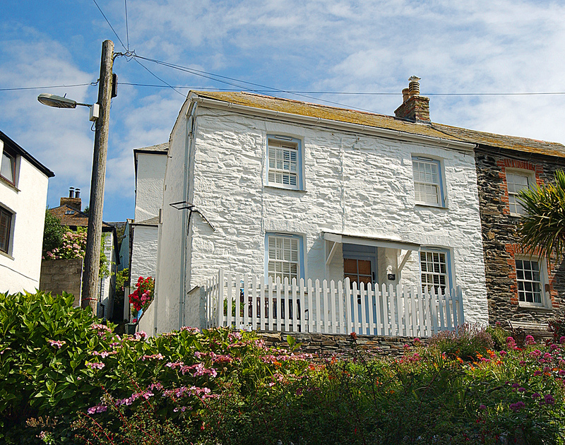 The whitewashed, stone exterior of Homelands, a holiday cottage located in the historic heart of Port Isaac.