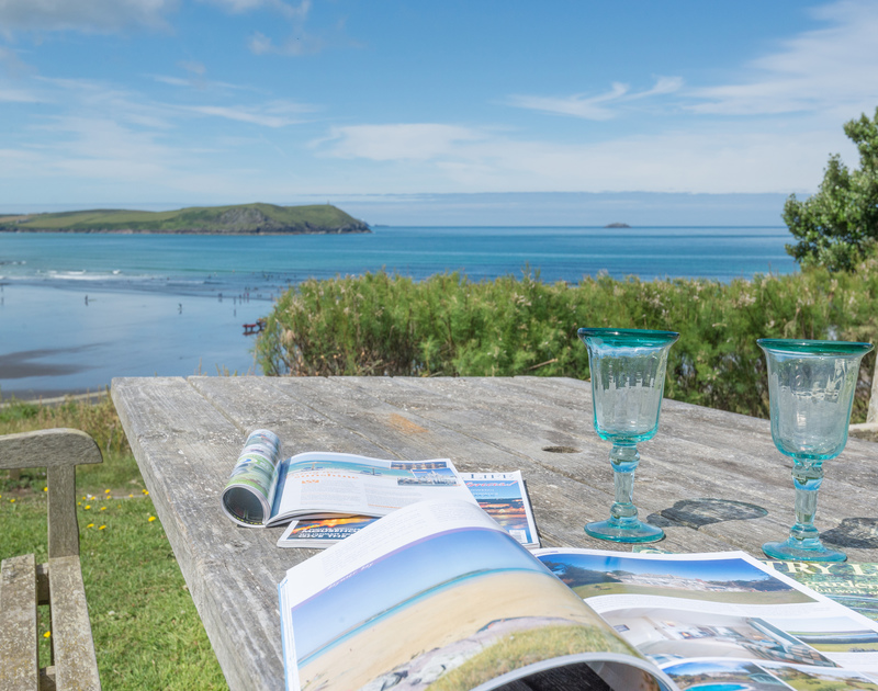 Relax in the garden of Low Cliff Cottage, a stunning holiday cottage in Polzeath, Cornwall, with table and adjacent benches.