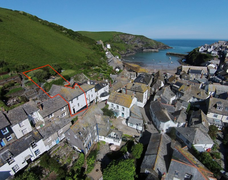 An aerial view of the harbourside location of 22 Church Hill, outlined in red, a self catering house in Port Isaac, Cornwall