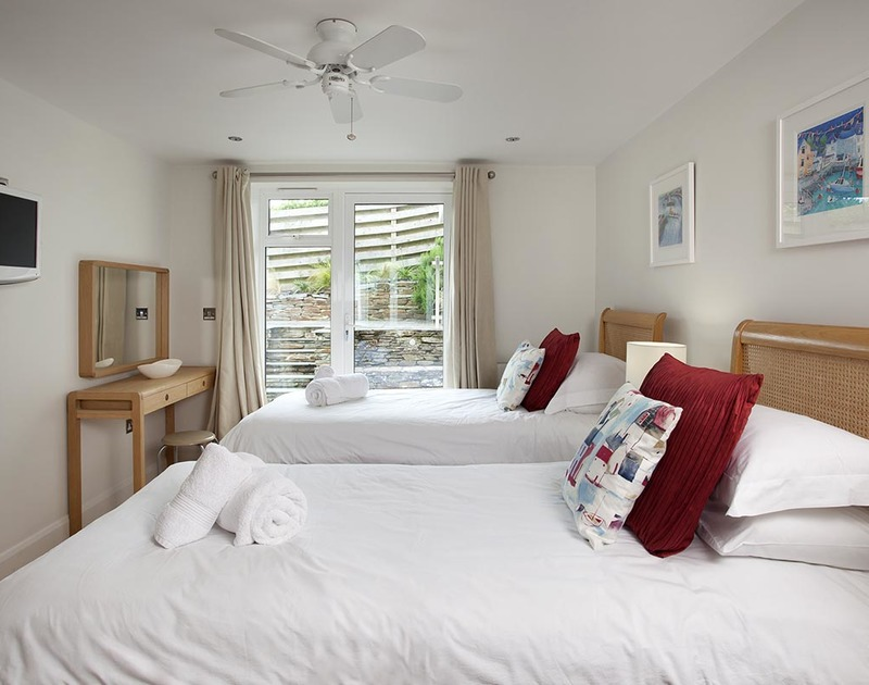 The third bedroom at Lyonesse has direct access to the sunny patio with views over Rock beach