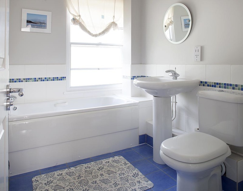 Shared family bathroom on the first floor of Lowenna Manor 4, with blue tiled flooring and decorative wall tiles in Rock, Cornwall