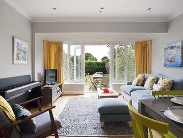 The light and airy living area with French windows that open onto the garden and patio in Lowenna Manor 4 in Rock, Cornwall