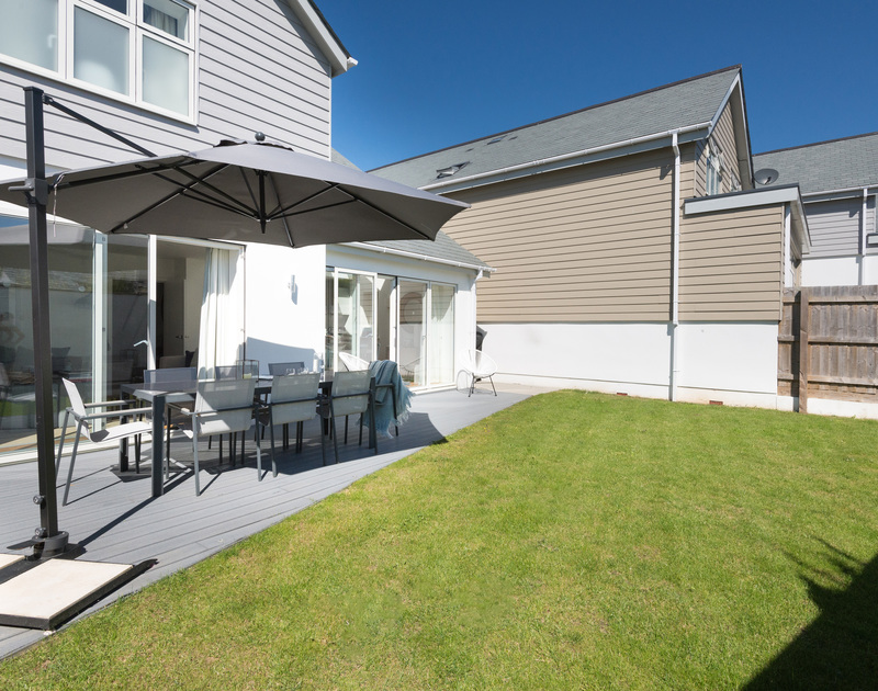 A well kept lawn, with high fencing and decking create a sheltered and private back garden, perfect for alfresco dining and enjoying some quiet time after a long day on the beach.