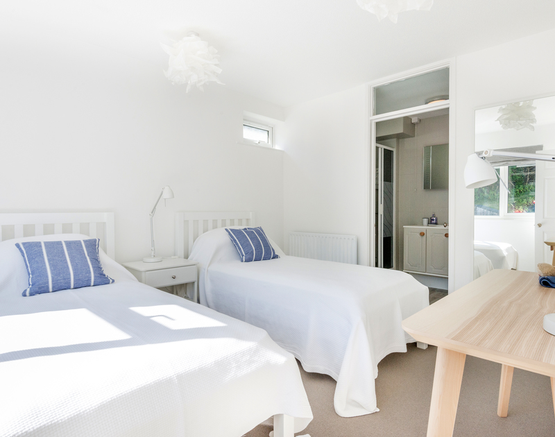 The ground floor twin bedroom at Tide Race in Daymer Bay is a light and sunny coastal inspired bedroom with an ensuite shower room.